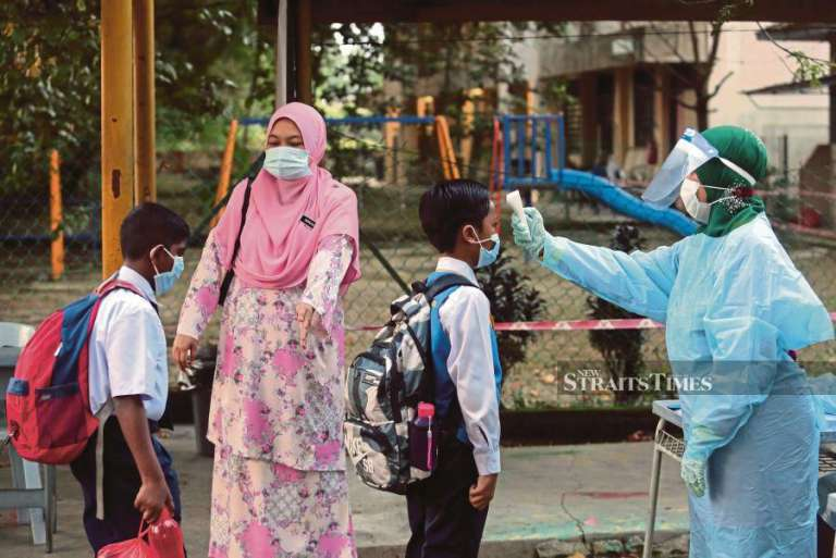 A teacher in Personal Protective Equipment checking the temperature of pupils entering SK Taman Klang Utama last month. -NSTP/File pic